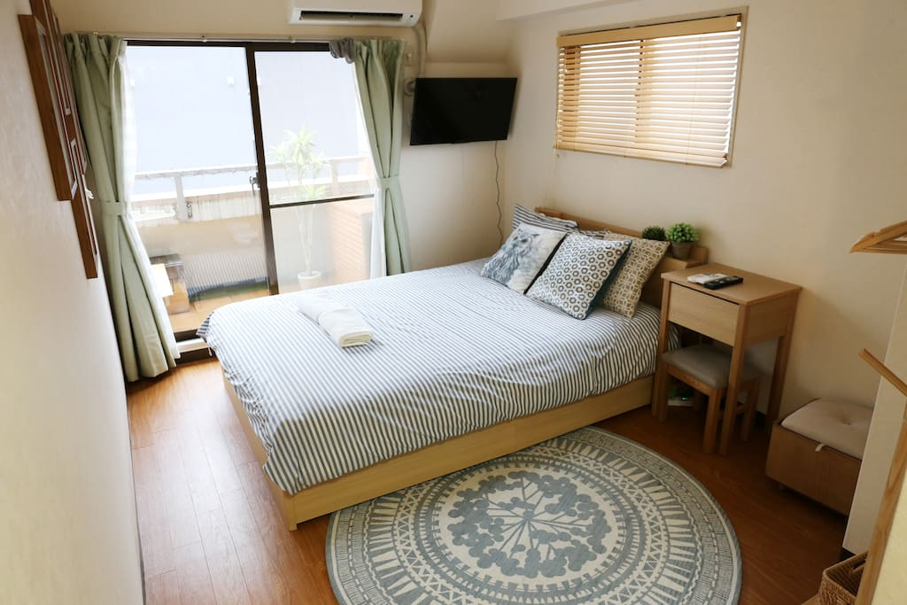 Bedroom with attached balcony, TV, beauty table for the ladies, and floor space for casual dining