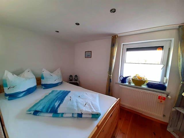 Schlafzimmer mit 1,40  Doppelbett und Kinderbett und Kleiderschrank, mit Blick auf's Wasser ( Haff)