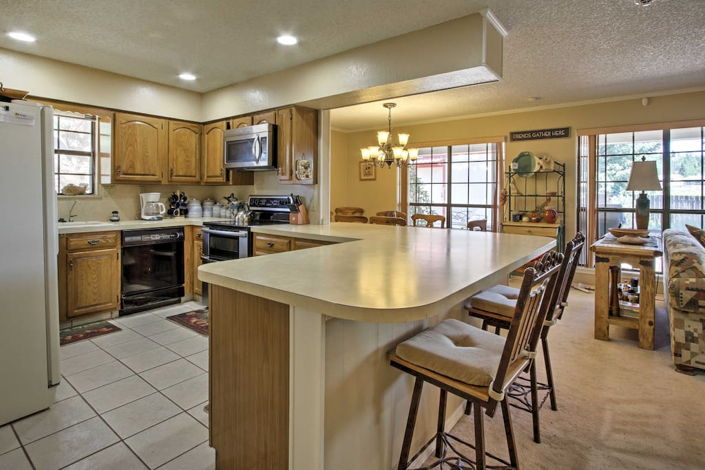 The fully equipped kitchen features a large wrap-around counter with 2-person bar stool seating and an adjacent 6-person dining room table.