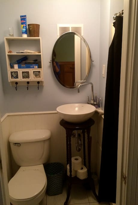 Small bathroom with shower, towels, hairdryer, first aid