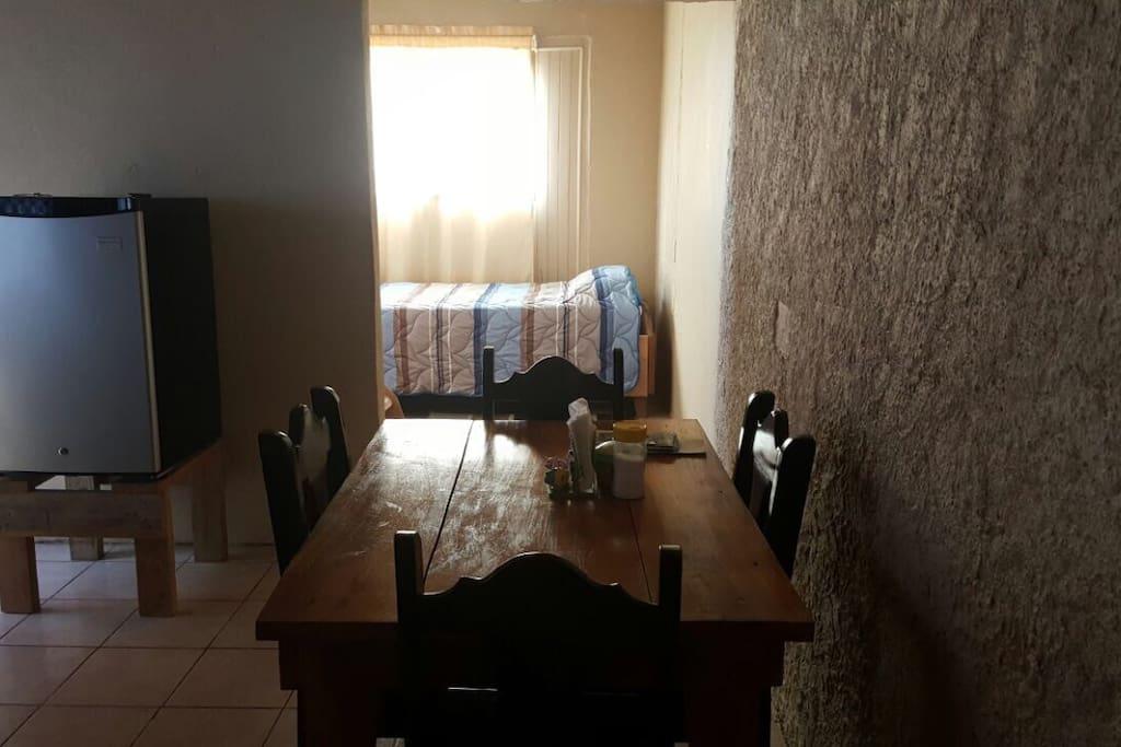 Mesa con cuatro sillas para disfrutar su comida.
