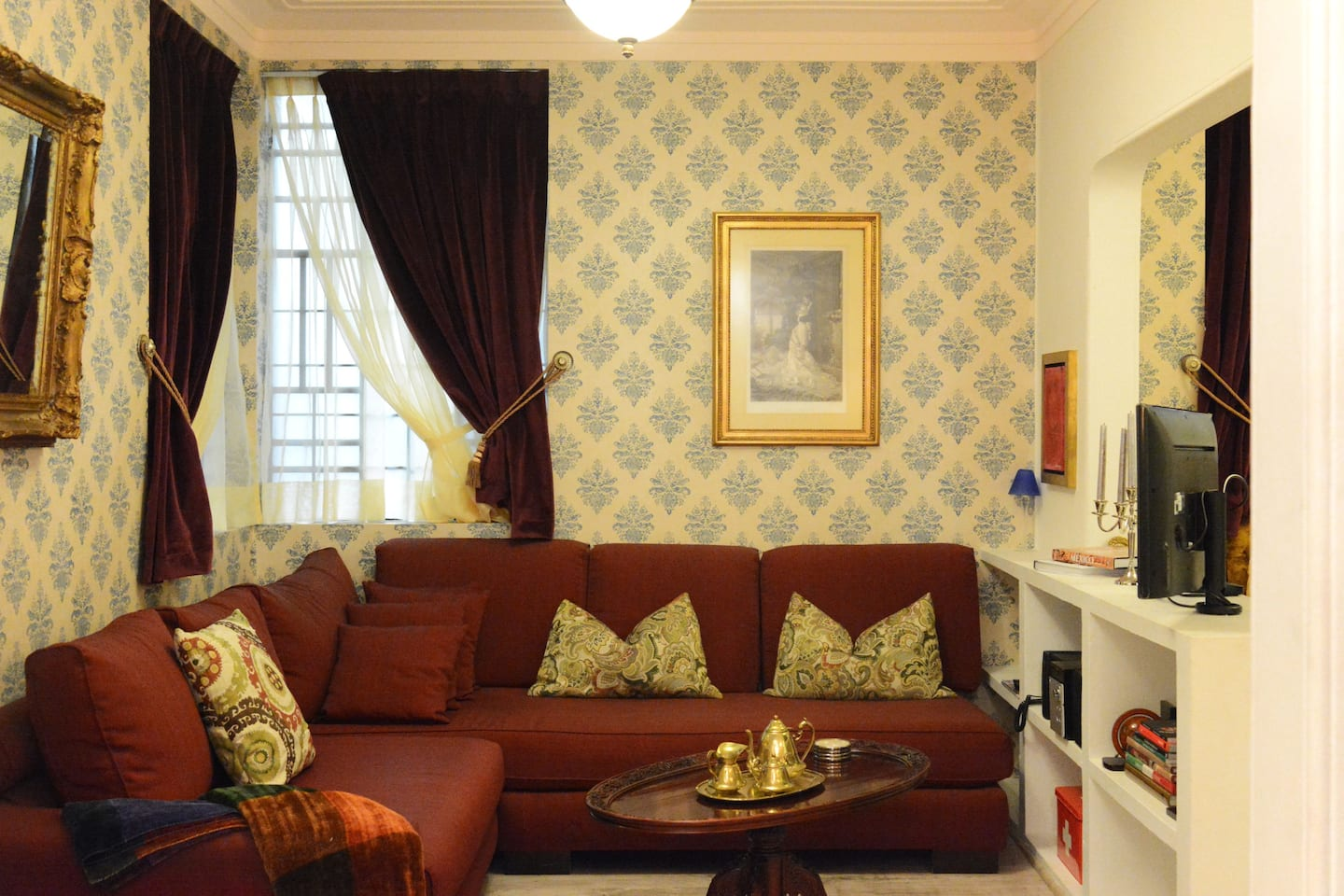 VRBO Mexico City: Vintage style living room with burgundy sofa and wallpaper