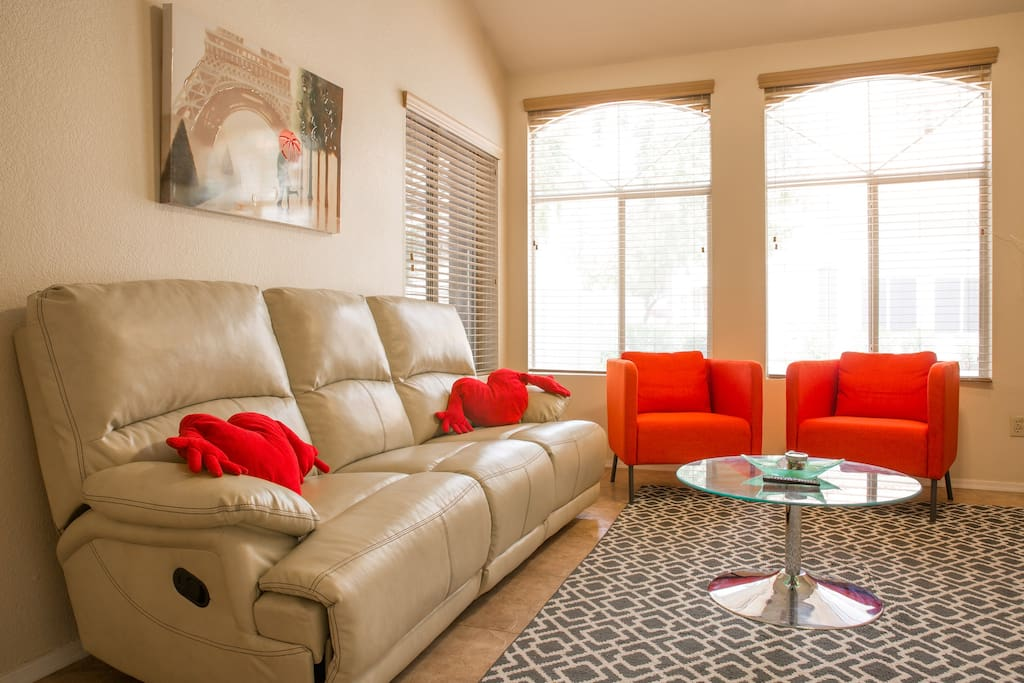 Comfortable living room with large space, a leather recliner sofa, and accent chairs.