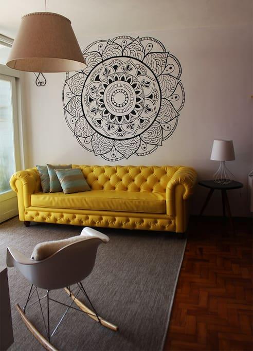 A nossa sala de estar tem uma mandala desenhada na parede, você pode meditar bem cedinho pela manhã ou no fim da noite, ou apenas olhar pra ela por alguns minutos, respirar fundo e mentalizar coisas boas. E sim, esse sofá é mesmo um espetáculo!!