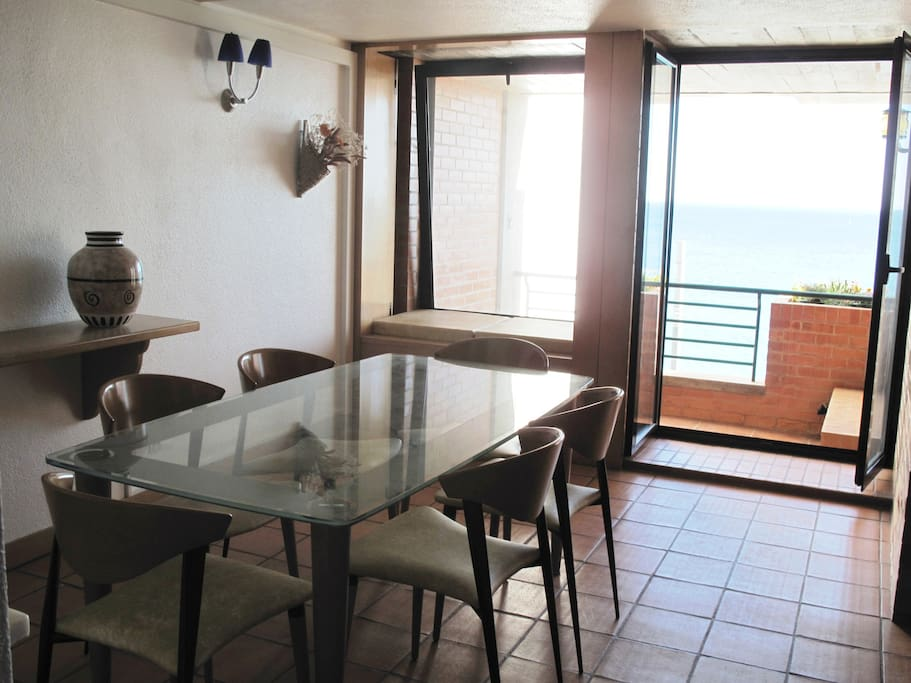 Sala de jantar junto à varanda com mesa de vidro e 6 cadeiras.
