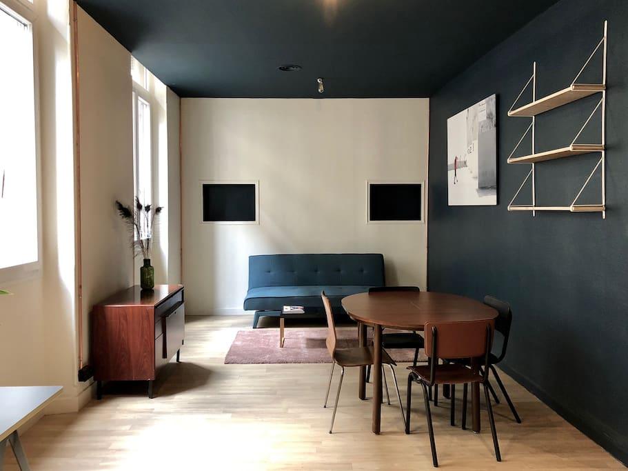 La salon de 20 metres carrés est équipé d'un clic clac pouvant accueillir 1 personne, d'une table pour les repas