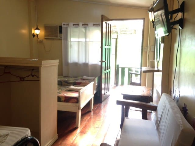 inside the room are 3 beds, 1 double and 2 single beds