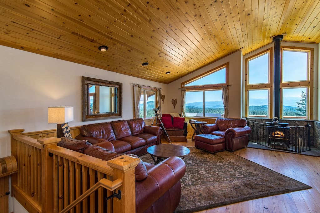 The main living room boasts leather furniture, sweeping views, and a wood stove