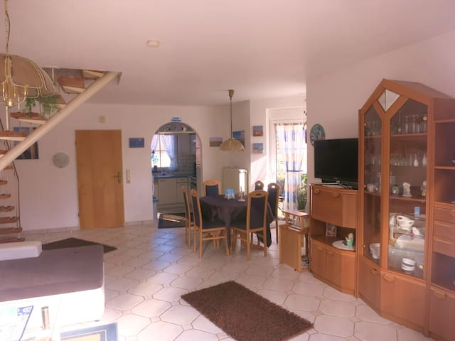 Wohnzimmer im EG mit Erker und Durchgang zur Küche und Diele, Esstischgruppe mit 6 Stühlen, Treppe zum OG