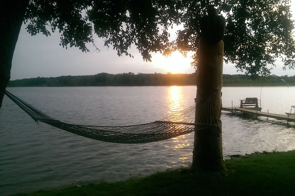 Lakeshore view with hammock, paddle boat and dock.