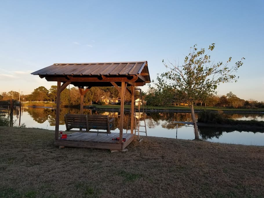 Covered gazebo with swing overlooking the water