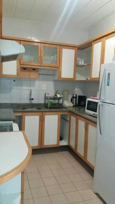 cozinha toda equipada geladeira fogão microondas. jogo de talheres  e jantar.
