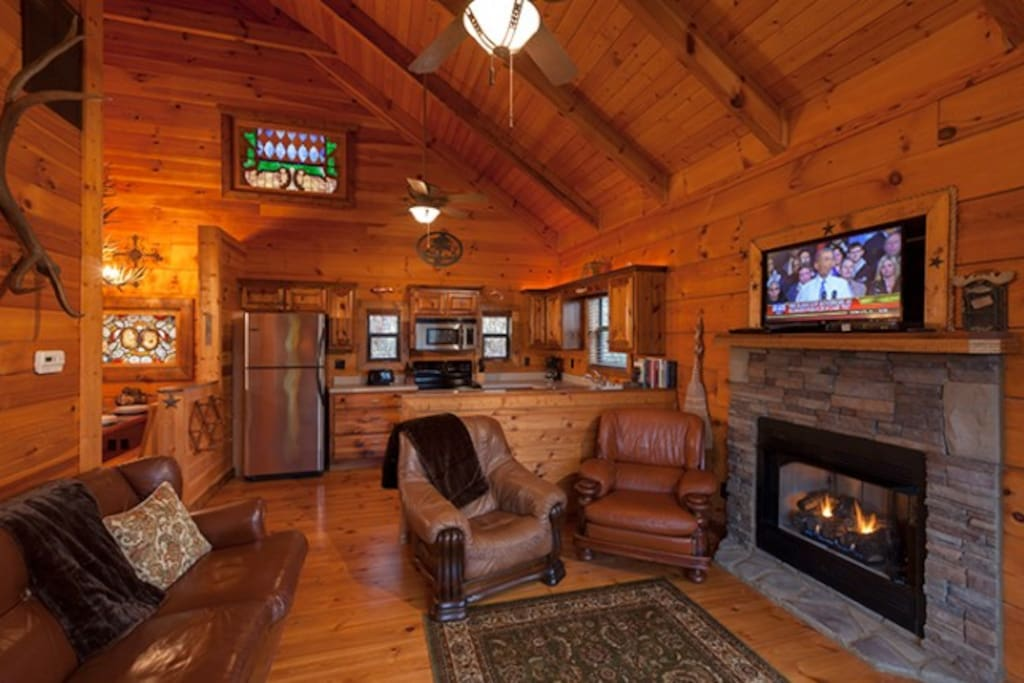 Cozy Living Area off Kitchen features Stone Gas Log Fireplace and Flat Screen TV