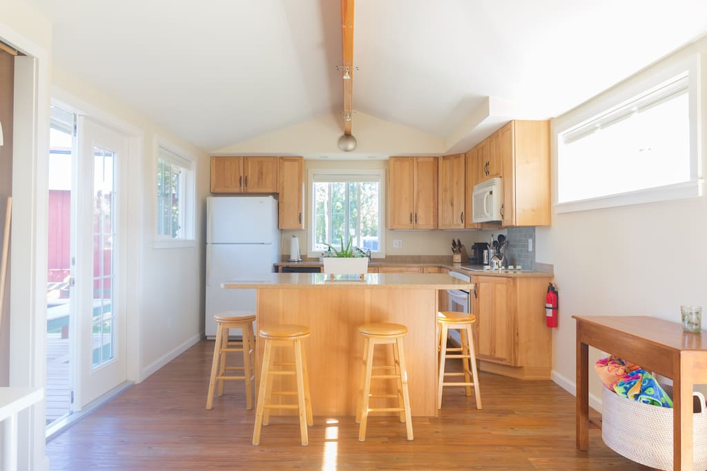 The kitchen is clean and fully stocked with cooking utensils, cookware, flatware, china, etc…  French doors open to deck and backyard