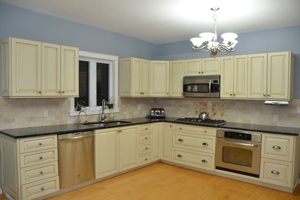 Open kitchen with stainless steel appliances, granite counter tops and custom millwork.