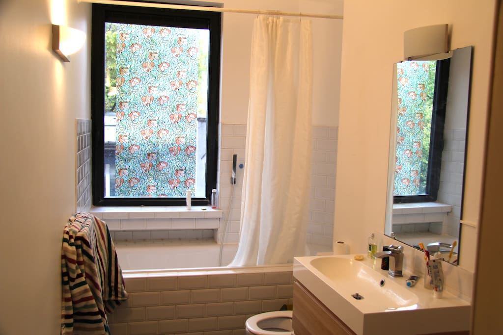 Full equiped bathroom with bathtub, shower and a big window