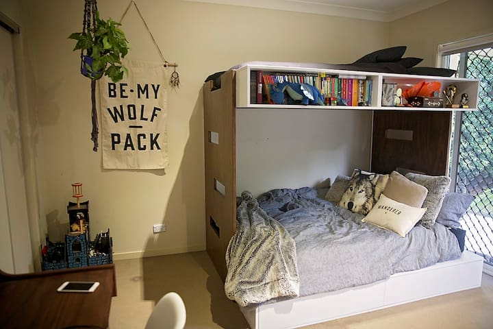 Children's Bedroom.  Double bed lower / single top. Desk with chair and separate chill out chair. Back door opens onto the backyard.