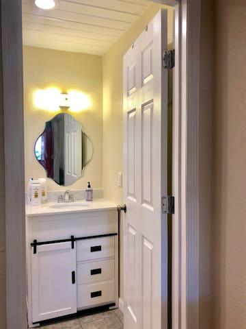 Bathroom door entrance. Big mirror, lots of lights