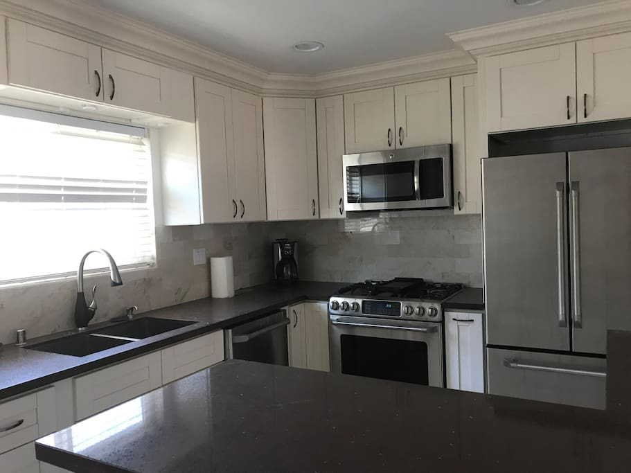 Fully renovated kitchen with stovetop, oven, microwave, coffee maker, and fridge/freezer