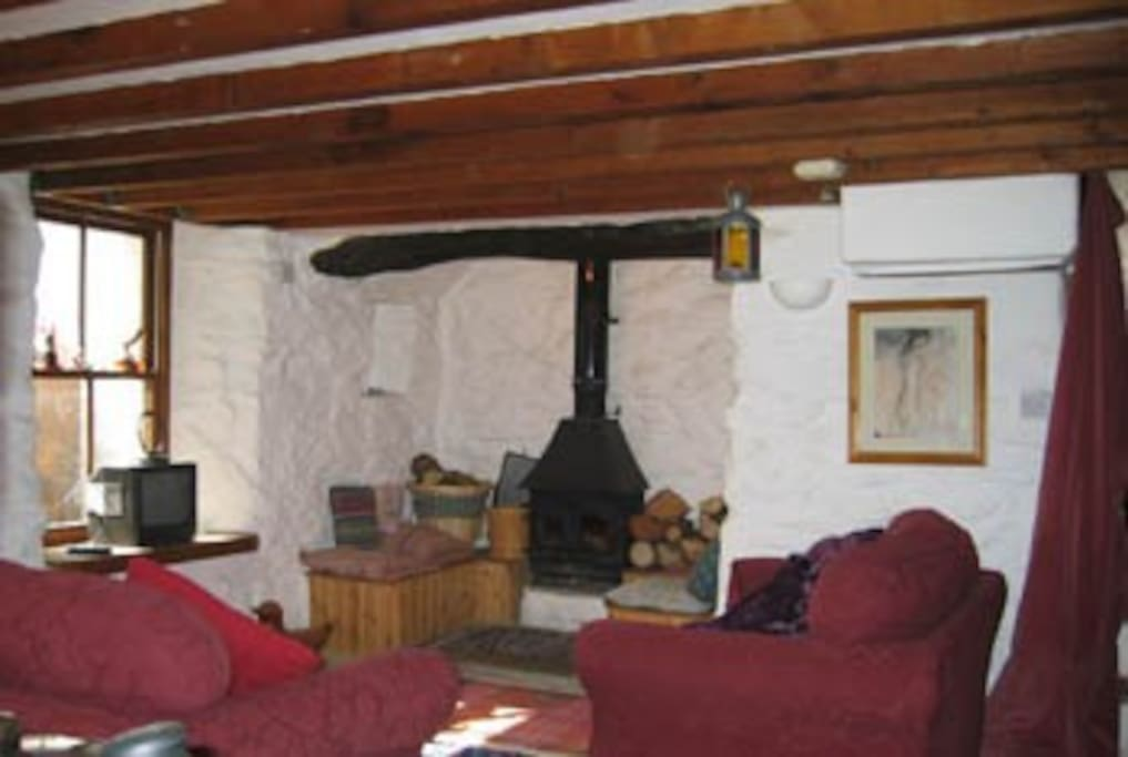 Living room with curvy stone walls and original inglenook...