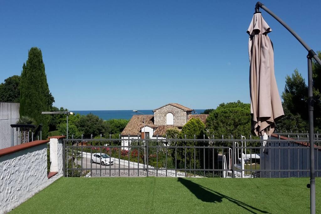 Solarium terrazzo superiore ad uso esclusivo con bellissima vista mare, alberi intorno e manto erboso sintetico