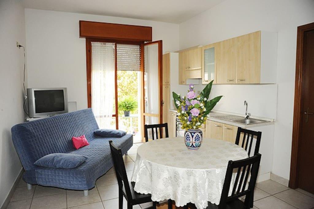 Cucina attrezzata con lavatrice, televisione, cassaforte e divano letto.