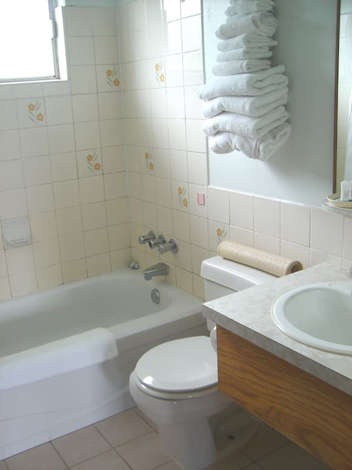 Stocked bathroom with full tub and towels.