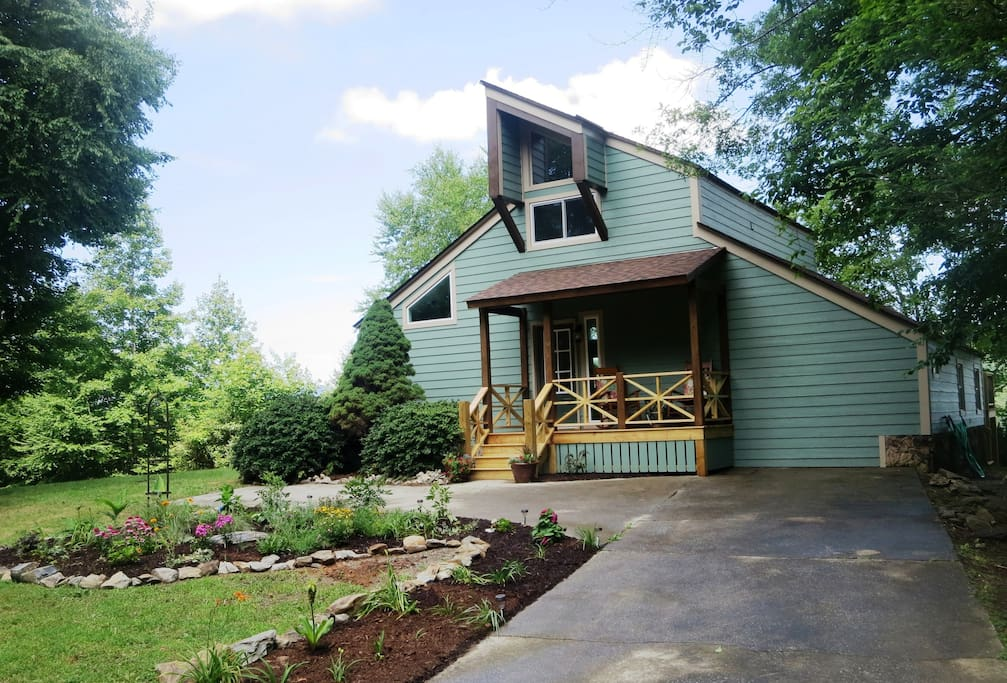 The rocking chair front porch and garden greet you as you approach the house.