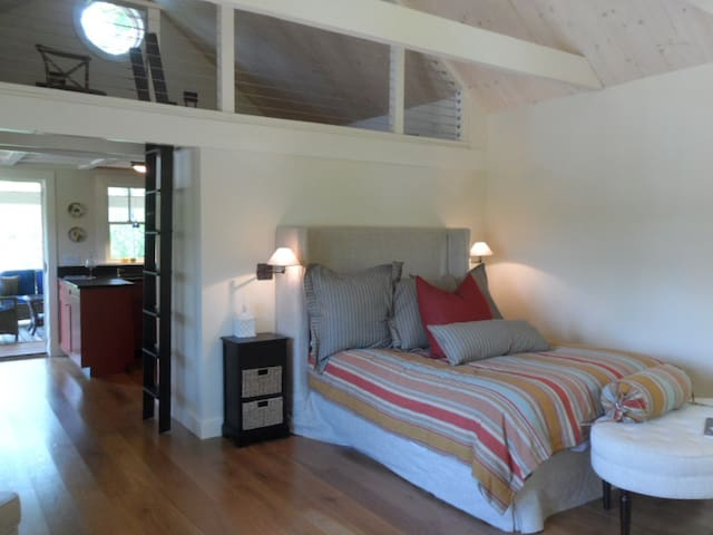 The comfortable queen bed with a view of the loft above.