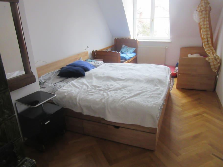 Schlafzimmer mit Doppelbett und Kinderbetten