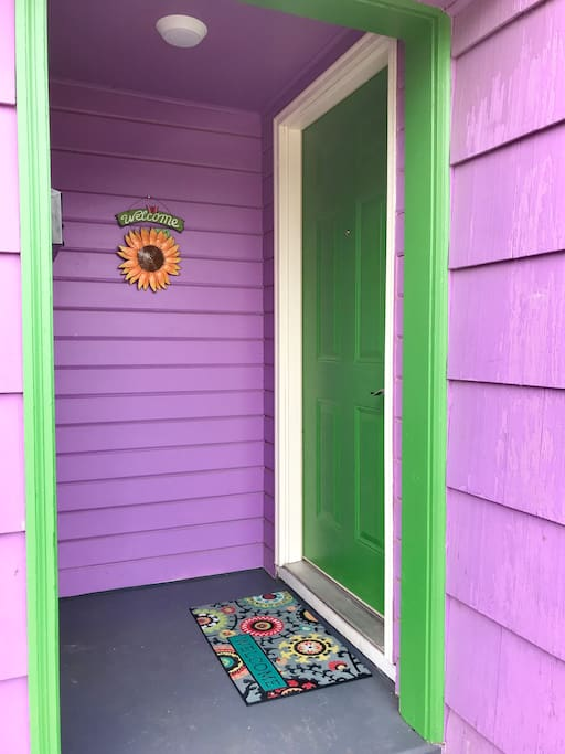 This is the front door inside the small alcove, right beside a green garage door in this purple duplex.