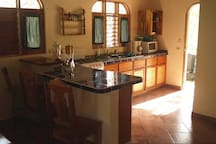 Open Kitchen.  4 burner stove with oven, microwave, blender and pots/pans.