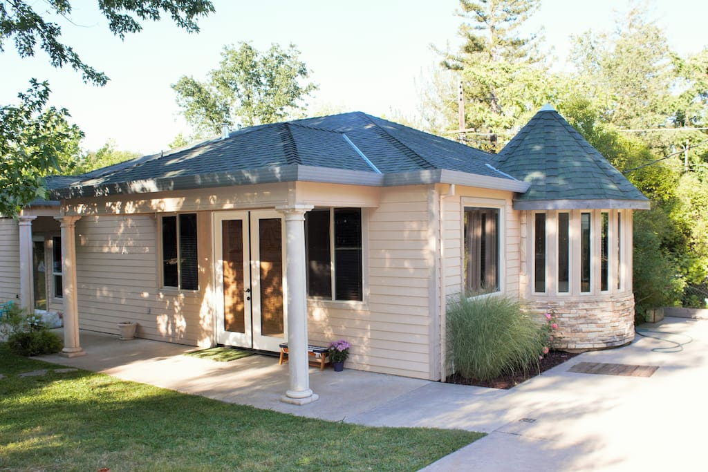 The guesthouse is nestled inside the backyard and features glass French door entry, small patio in the front and 180 degree bay window.,