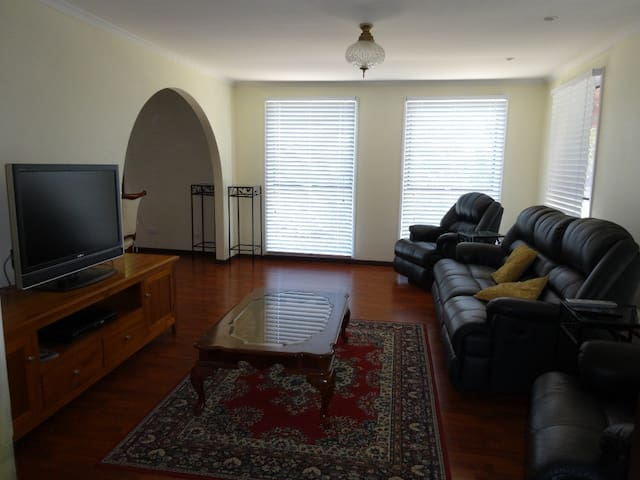 Living room with seating for 5 people, large flat screen TV and DVD player.