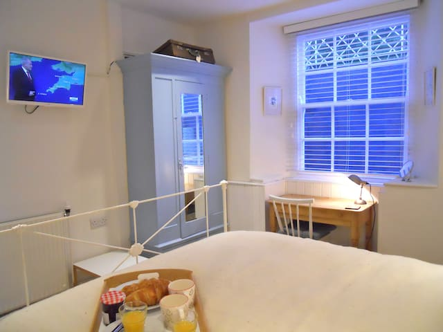 The bedroom has a small vintage wardrobe, antique desk/dressing table and wall-mounted smart TV