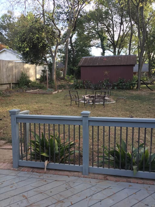 Large fenced in backyard with fire pit, outdoor table, and grill (shared space)