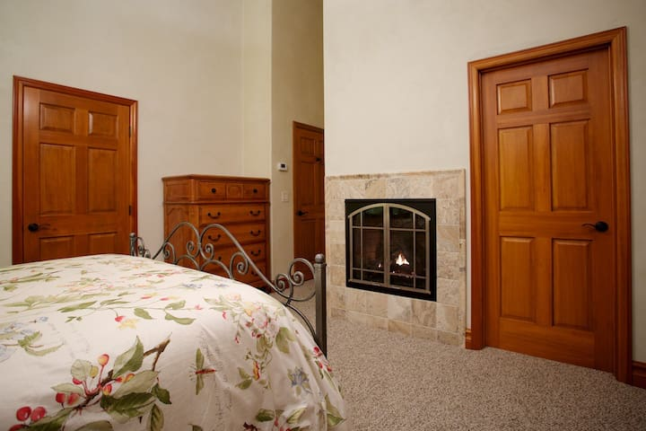 Gas Fireplace operated by a simple on/off wall switch. To the left of the Chest of Drawers is the closet and to the right is the bedroom entrance. To the right of the fireplace is the bathroom.