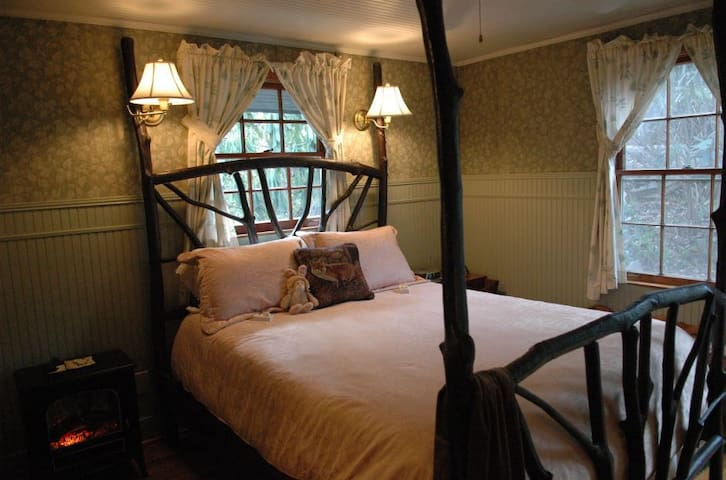 The Woodland Room in the Black Bear Cottage in the Woods - handcrafted four poster bed is laurel branches