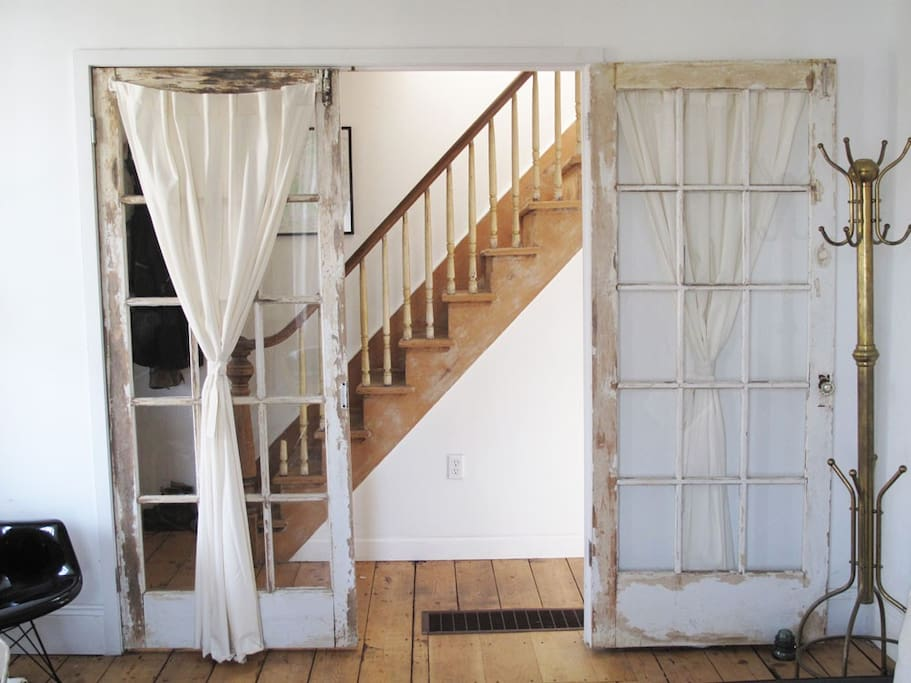 the original wooden stair seen from the living room with sleeper sofa & Danish wood stove