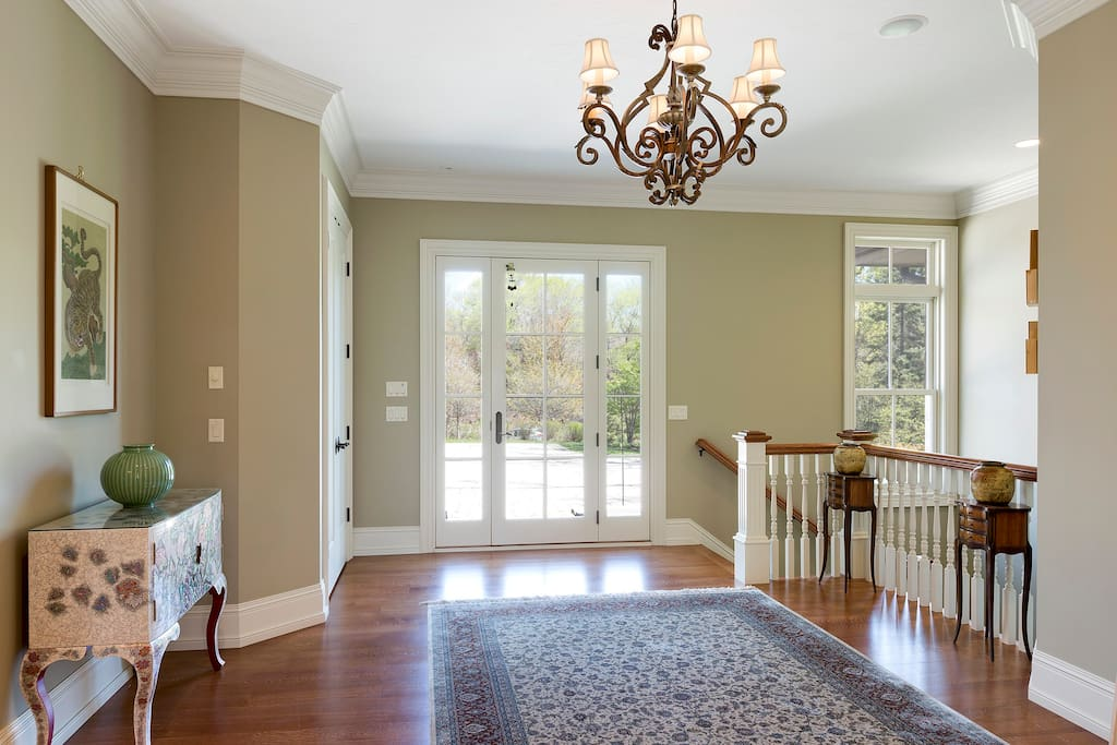 Bright, open foyer with hardwood floors and custom finishes.