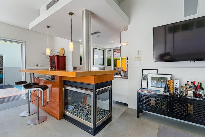 Perch at the striking kitchen bar, featuring a built-in gas fireplace.