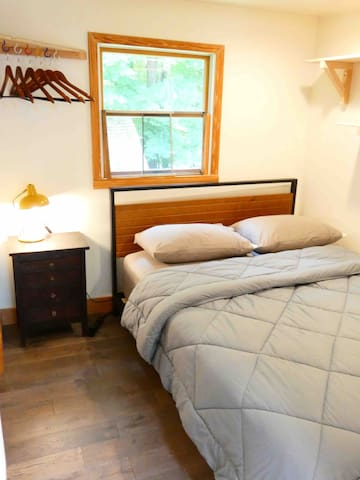 """Queen Bedroom.  Small, efficient and comfy.  Nice foam topper on foam mattress makes bed super comfy.  Limited additional space with corner open """"closet"""" and open shelving.  Off of kitchen and utility/laundry rm."""