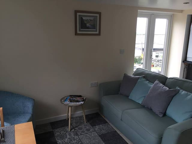 Living space with  comfy Sofa bed and matching chair and access to the rear garden