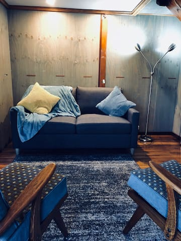 Comfortable sofa bed in lounge area.  Walls are made with up cycled plywood.