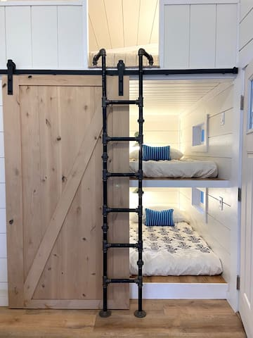 """Two twin mattresses in a bunk style is serves as the third room. A fun """"barn style"""" door creates privacy."""