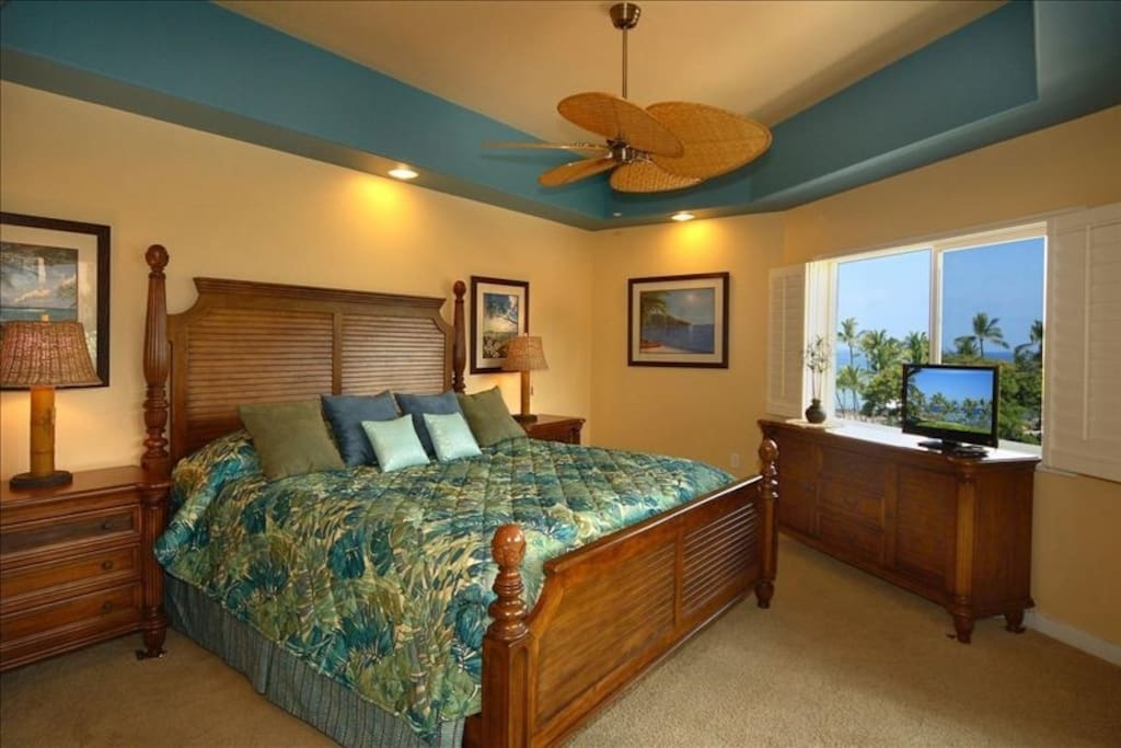 Master bedroom overlooking ocean...gorgeous views with Plantation Shutters and has sliding doors to beautiful lanai.