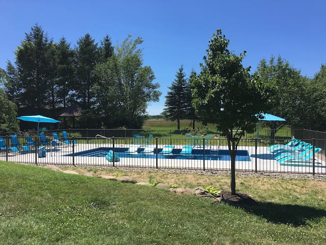 BACKYARD/POOL: Super-private 3 acres surrounded by farmland.  In-ground heated pool, deep&shallow ends, fence, self-locking security gate, umbrellas, rafts, pool loungers, deluxe noodles, pool/beach towels, white picnic table  in background.