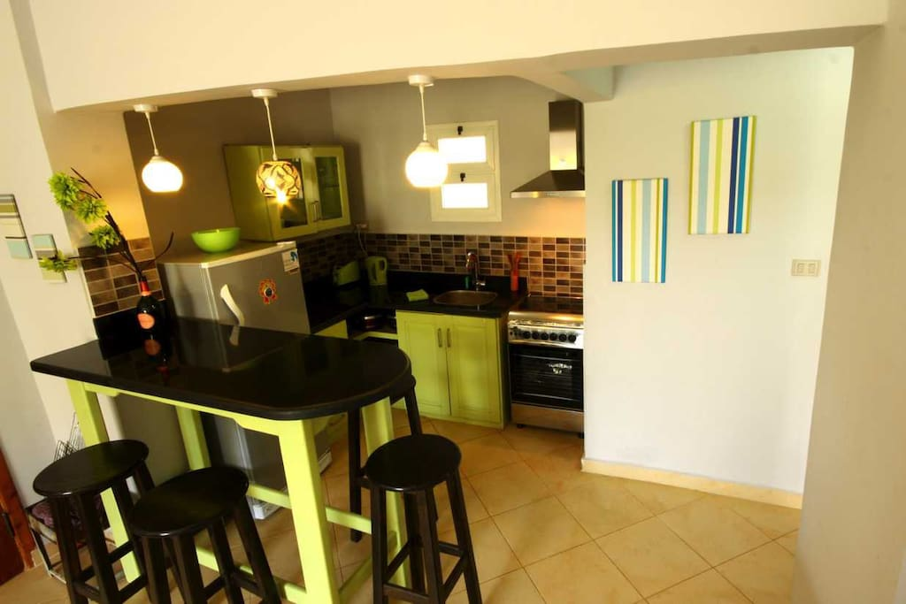 Open plan kitchen with gas oven, 4 hobs, extractor fan, kettle, toaster, large fridge/freezer.
