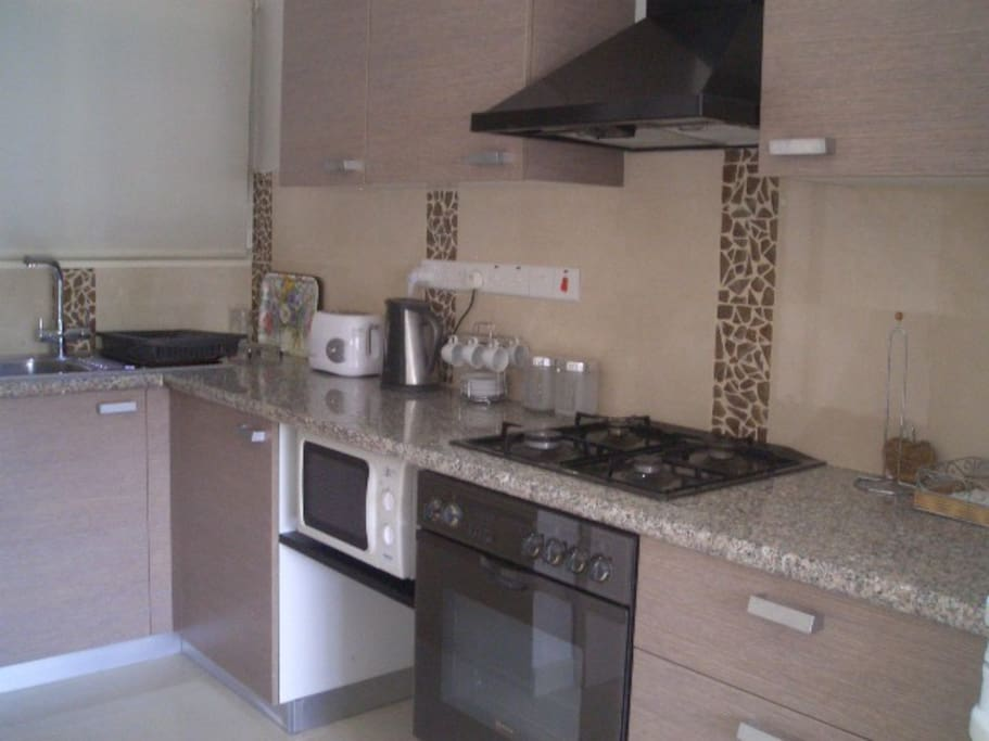 Kitchen with gas hob/microwave and other electrical appliances.