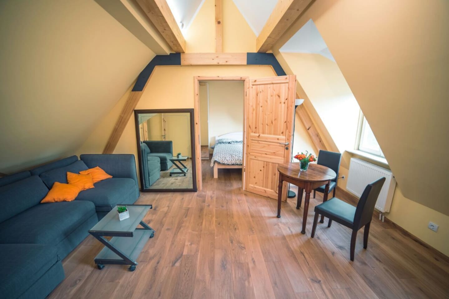 Wohnzimmer mit Schlafsofa und dahinter liegendem Schlafzimmer